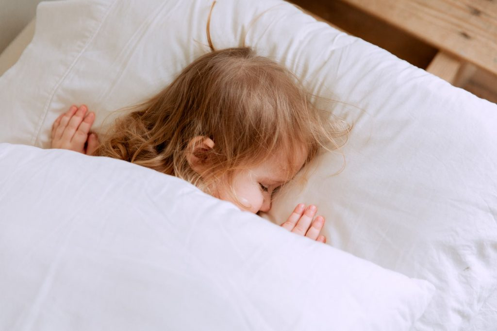 photo of child laying on bed