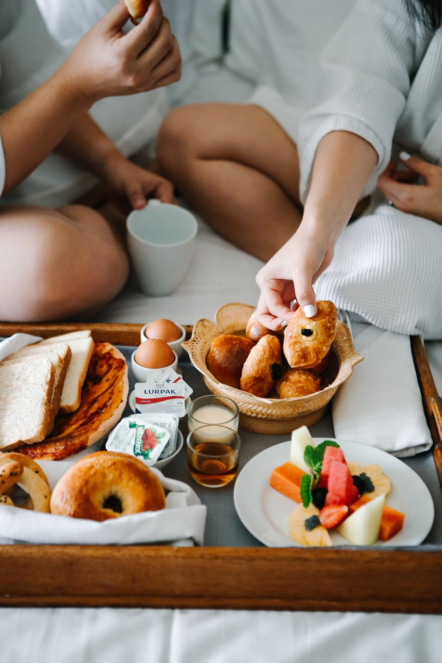 couple eating breakfast on the bed
