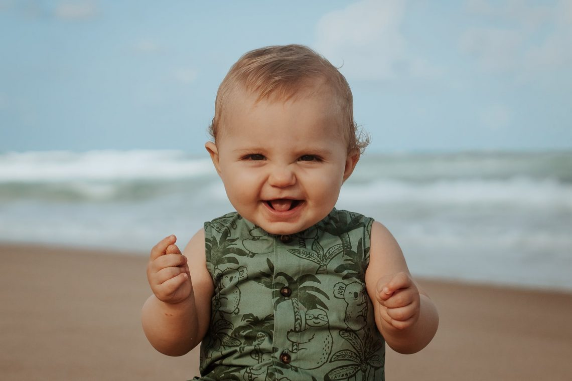 cheerful baby on sandy sea shore in stormy weather